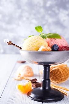 Dessert glacé au citron et à la fraise dans un bol en métal avec gaufrette et baies sur bois