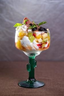 Dessert avec de la glace et des fruits dans un verre.