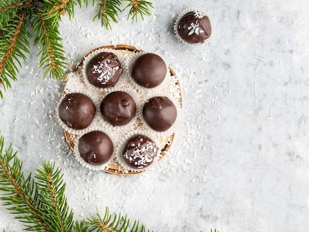 Dessert d'hiver, truffes au beurre d'arachide sans sucre en bonne santé recouvertes de chocolat noir et de noix de coco, noël et nouvel an, branches de sapin, assiette en bois