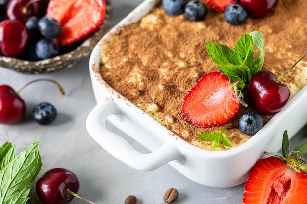 Dessert italien classique tiramisu décoré de fraises, cerises et menthe sur fond blanc.