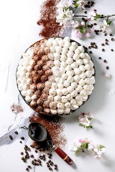 Dessert italien traditionnel tiramisu sans gluten fait maison saupoudré de poudre de cacao décoré de pommier en fleurs et de grains de café sur une surface en marbre blanc. vue de dessus, mise à plat. espace de copie