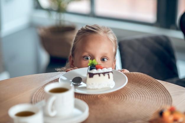 Dessert. une jolie fille blonde à la recherche d'anticipation tout en regardant la tranche de gâteau