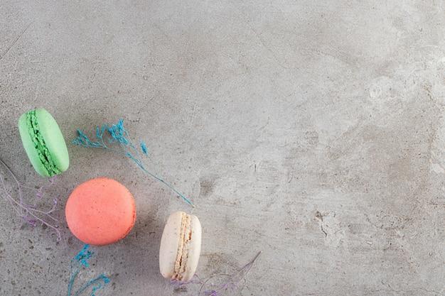 Dessert macarons colorés placés sur une table en pierre.