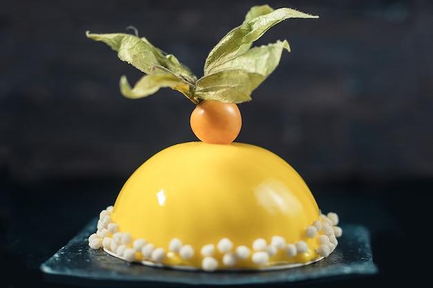 Dessert mousse au citron avec glaçage miroir jaune. fond sombre.
