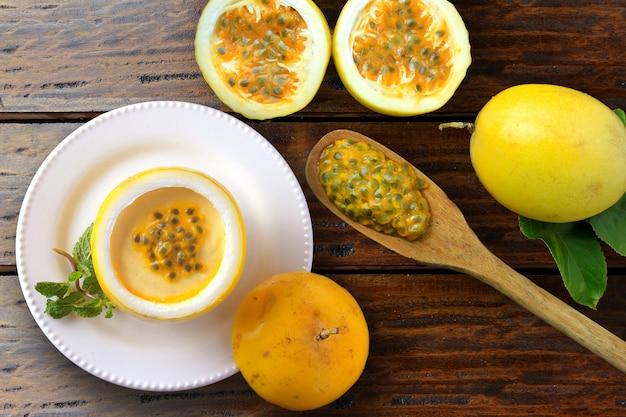 Dessert mousse de fruits de la passion à la croûte de fruits sur assiette, table rustique en bois