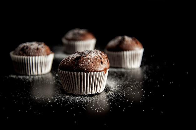 Dessert muffin sur fond noir avec du sucre en poudre