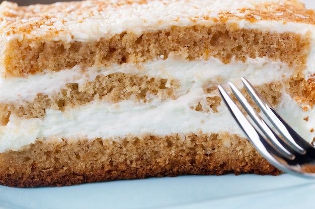Dessert multicouche sucré et délicieux à base d'un grand nombre d'ingrédients, un morceau de gâteau avec un grand nombre de calories à manger à la fin du déjeuner, une pâtisserie à base de gâteau et de crème