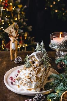 Dessert de noël, rouleau de meringue décoré de maison en pain d'épice
