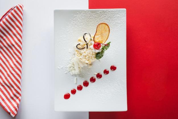 Dessert orange crémeux sur une surface colorée de rouge et blanc.