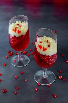 Dessert panakota gelée à la grenade closeup décoré de crème en verre