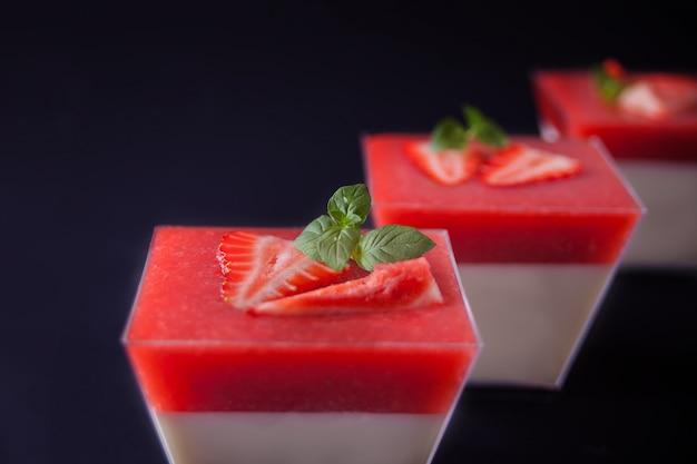 Dessert panna cotta aux fraises fraîches sur fond noir