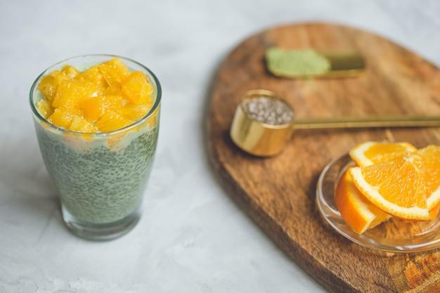 Dessert de pouding au thé vert matcha aux graines de chia avec orange en verre