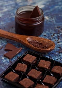 Dessert sablé au chocolat et biscuit sur planche bleue avec pot de chocolat liquide et cuillère en bois