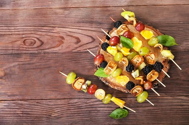 Un dessert sain sur des brochettes à base de mini crêpes, mûres, raisins et kiwi sur une table en bois marron.
