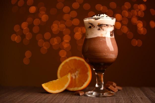 Dessert savoureux avec sauce au chocolat, crème et orange, sur table