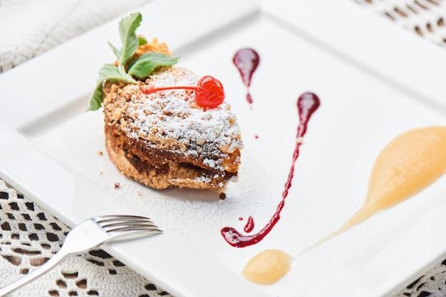 Un dessert sucré composé de crumble avec de la compote de pommes et une garniture aux cerises servi sur une plaque blanche