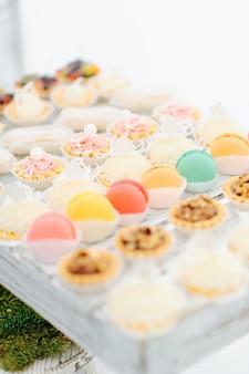 Dessert sucré délicieux petits gâteaux, macarons et biscuits au bar à bonbons sur la table. délicieux buffet sucré. décorations de vacances de mariage