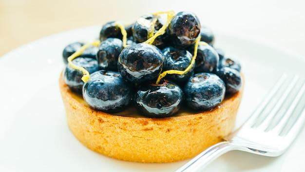 Dessert sucré avec une tarte aux myrtilles dans une assiette blanche