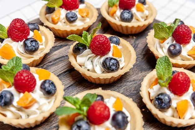Dessert tartelettes aux fruits et baies assortis sur plateau en bois. gros plan de délicieuses pâtisseries tartes gâteaux colorés avec de la crème de myrtille et fromage framboise naturelle. restauration boulangerie française.
