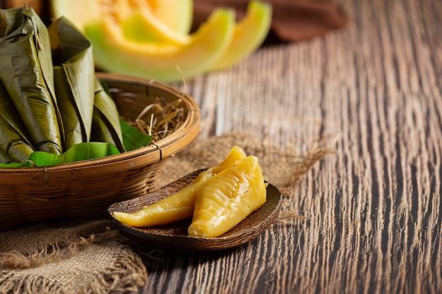 Dessert thaïlandais. pâtisseries vapeur au cantaloup enveloppées dans un cône de feuille de bananier