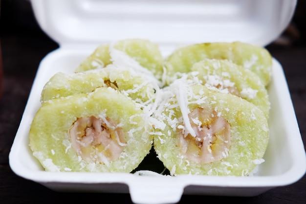 Dessert thaïlandais sucré, banane dans des morceaux de riz cuit à la vapeur sur une boîte en mousse blanche