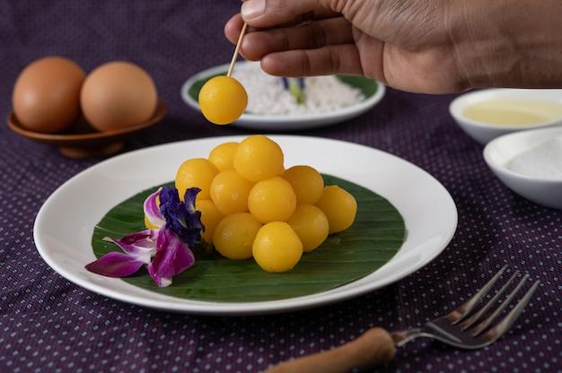 Dessert thong yod sur une feuille de bananier dans une assiette blanche avec des orchidées et une fourchette