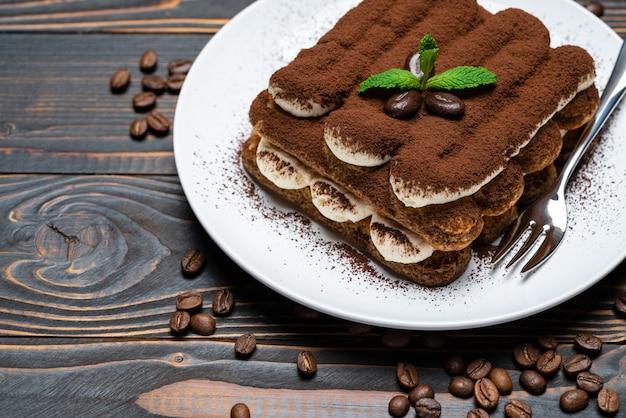 Dessert tiramisu classique sur plaque en céramique sur fond de bois