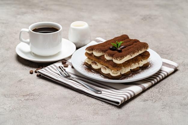 Dessert tiramisu classique sur plaque en céramique, lait ou crème et tasse de café sur une surface en béton