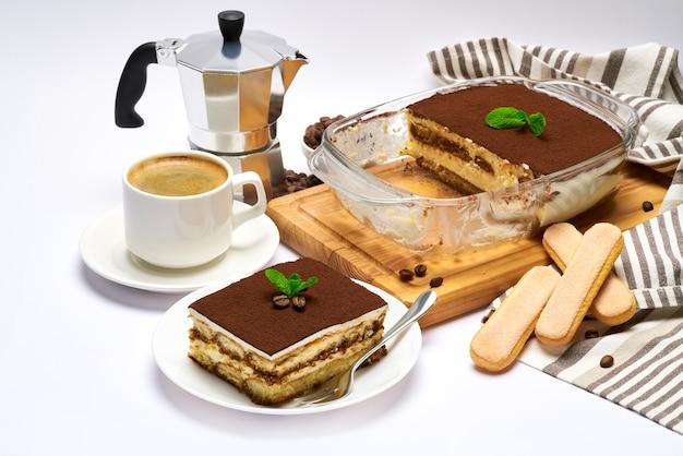 Dessert tiramisu italien traditionnel dans un plat de cuisson en verre portion sur assiette et tasse de café isolated on white