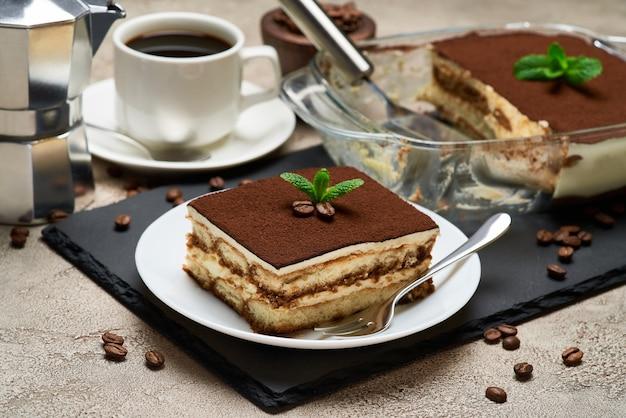 Dessert tiramisu italien traditionnel dans un plat de cuisson en verre et portion sur table en béton gris