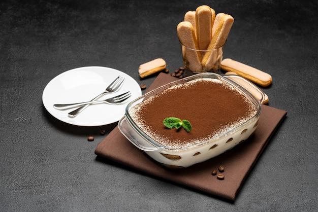 Dessert traditionnel tiramisu italien dans un plat de cuisson en verre et biscuits savoiardi sur fond de béton ou table