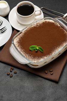 Dessert traditionnel tiramisu italien dans un plat de cuisson en verre et tasse de café expresso chaud frais sur fond de béton ou table