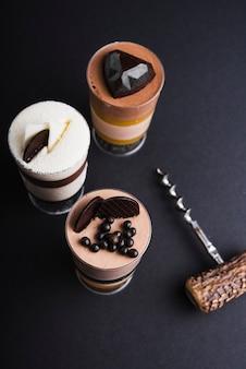 Dessert de trois mousses au chocolat dans un bocal en verre sur fond noir