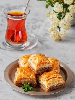 Dessert turc baklava aux noix et noisettes, et thé turc noir fort