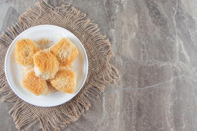 Dessert turc kadayif sur une assiette sur une serviette sur du marbre.