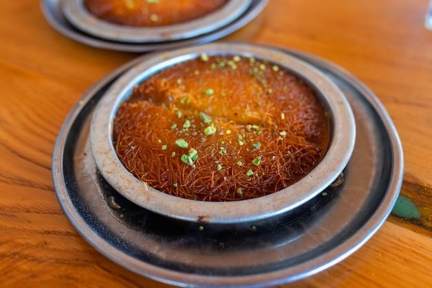 Dessert turc kunefe, kunafa, kadayif avec poudre de pistache et fromage, servi chaud, très sucré.