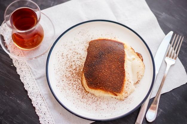 Dessert turc traditionnel kazandibi avec cannelle en poudre et thé turc