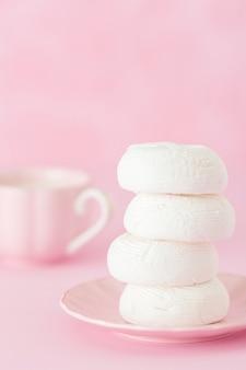 Dessert de zéphyr blanc sur assiette rose, tasse de café au lait sur fond rose pastel.