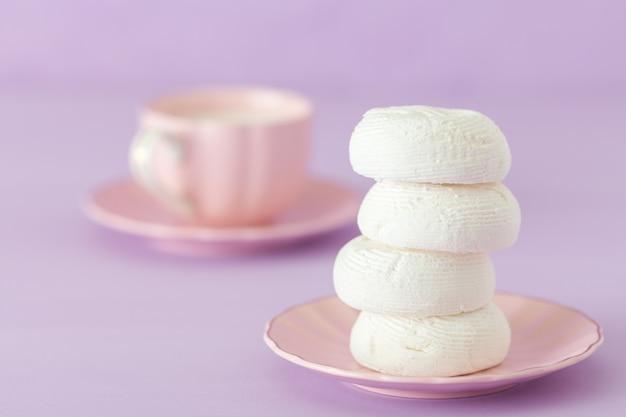 Dessert de zéphyr blanc sur assiette rose, tasse de café au lait sur fond violet pastel.