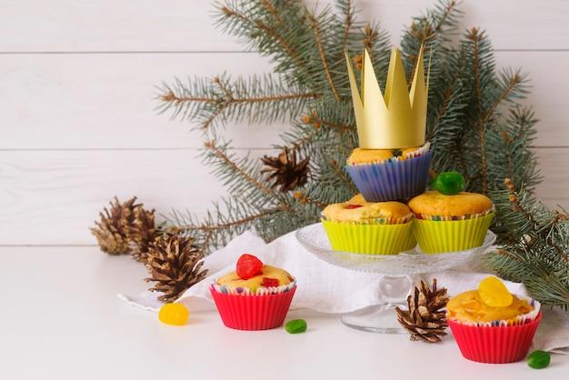Desserts du jour de l'épiphanie sur la table avec couronne et épicéa
