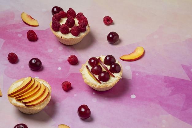 Desserts d'été avec des fruits en tranches et des baies sur fond rose