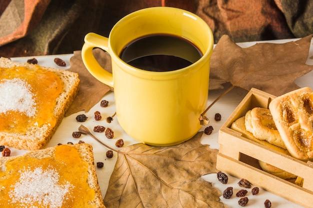 Desserts et feuilles près de la tasse de café