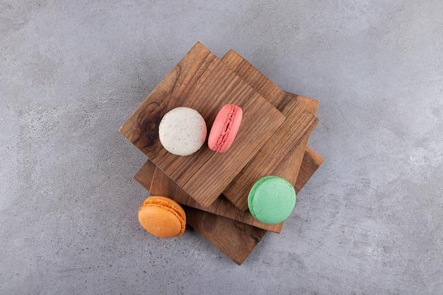 Desserts macarons sucrés colorés placés sur planche de bois.