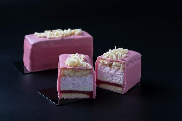 Desserts à la mousse en tranches avec biscuit aux amandes, coolie aux fraises et mousse aux fraises recouvert de glaçage au chocolat rose