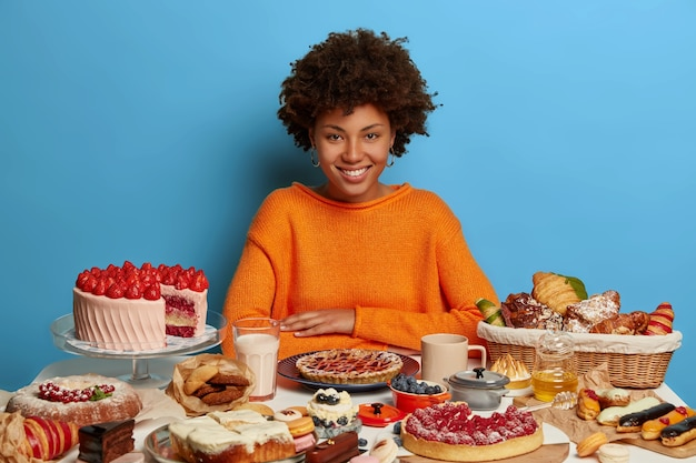 Desserts, restauration rapide, concept de mode de vie malsain. heureux modèle à la peau sombre en pull orange, aime faire la fête, n'a pas de régime, stimule l'humeur avec des plats sucrés, isolés sur un mur bleu.