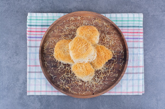 Desserts sucrés turcs dans une assiette en bois sur pierre.