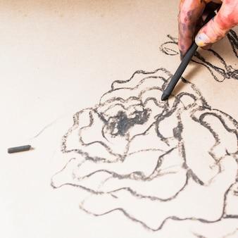 Dessin abstrait avec bâton de charbon de bois à la main