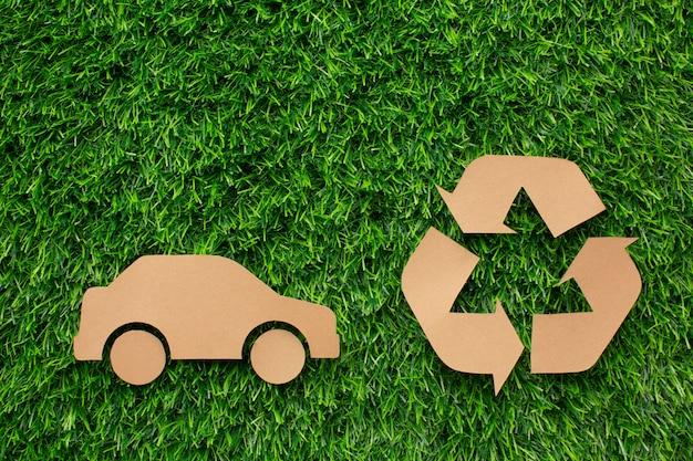 Dessin animé voiture et recycler signe dans l'herbe
