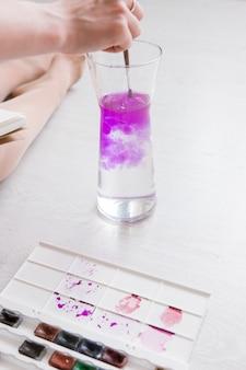 Dessin à l'aquarelle. l'artiste lave le pinceau. éclaboussures colorées et vagues de couleur dans l'eau. peinture d'artiste avec palette et pinceau.