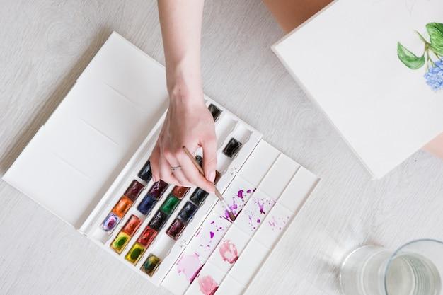 Dessin à l'aquarelle. peintre travaille avec croquis. oeuvre colorée de fleur sur papier blanc. peinture d'artiste avec palette et pinceau.